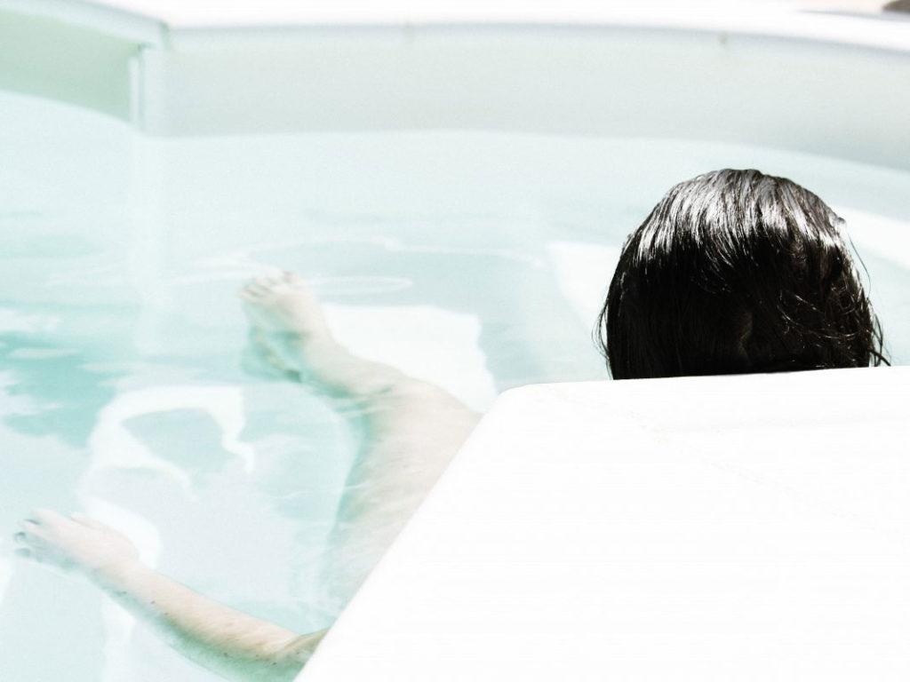 浴槽と座位で入浴する女性の後ろ姿