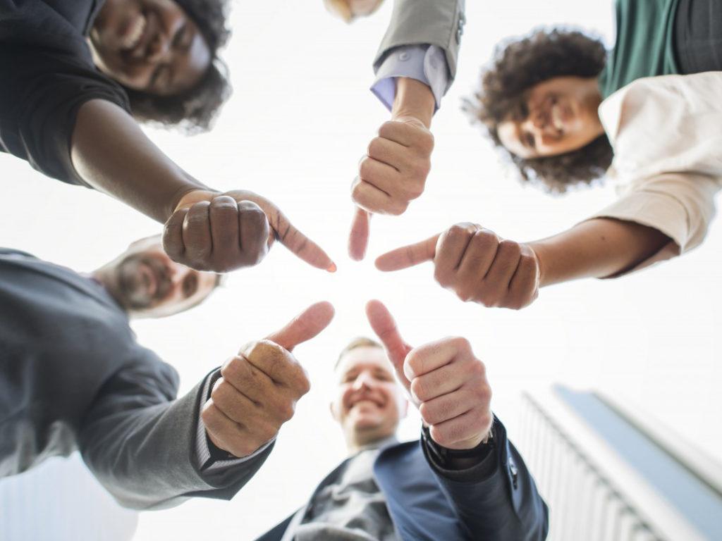 ダイバシティ 円陣を組み親指を上げるしぐさをする白人アメリカ人男性とアフリカ系アメリカ人女性
