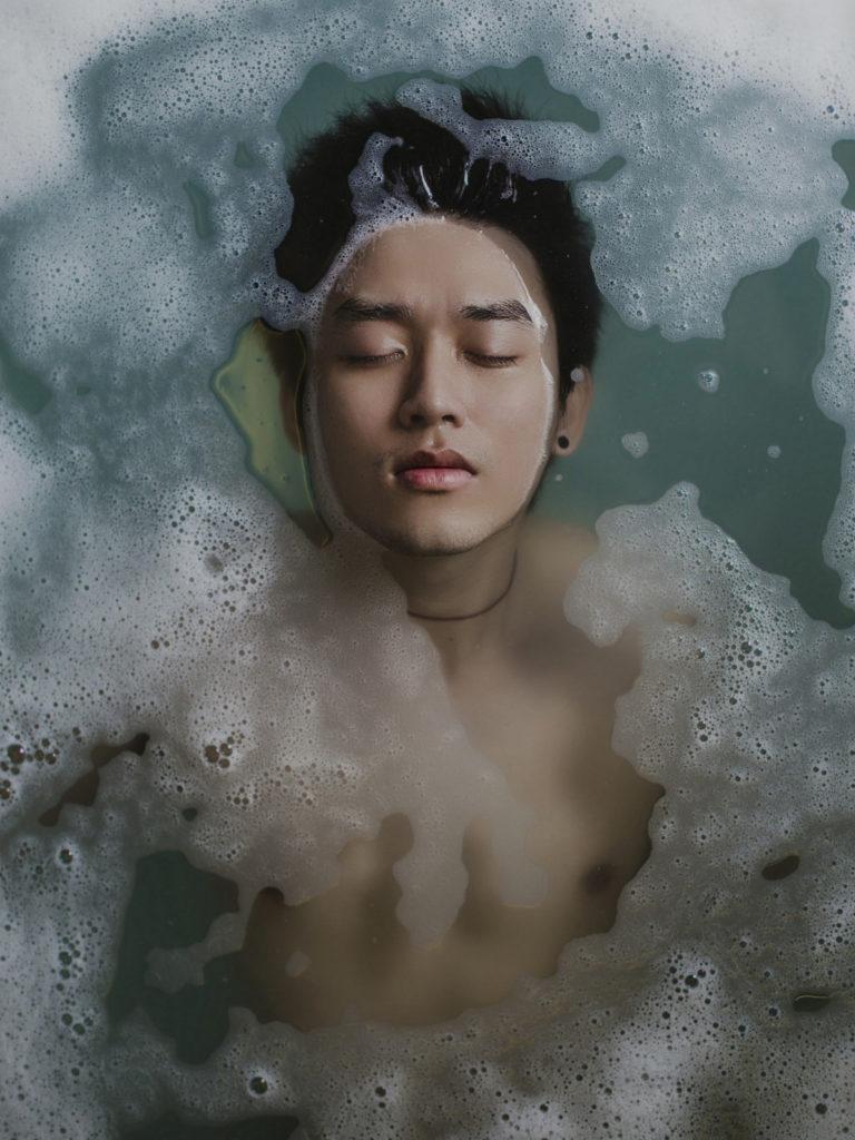 バスバブルを入れた浴槽で全身浴し、眼を閉じて顔だけ出す青年