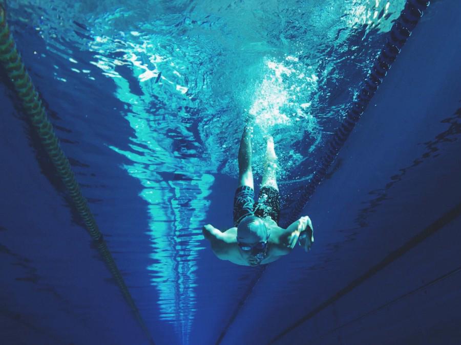 プールで泳ぐ男性を水中から撮影