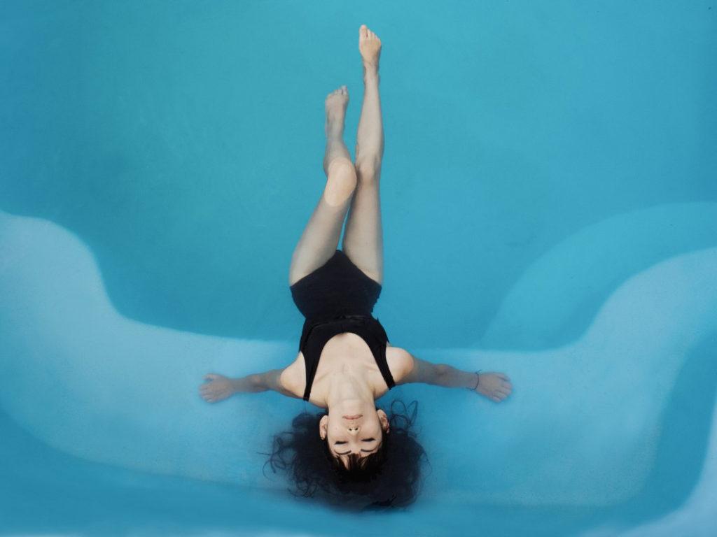 青い浴槽の水に水着姿で仰向けに浸り目を閉じている若い黒髪の女性