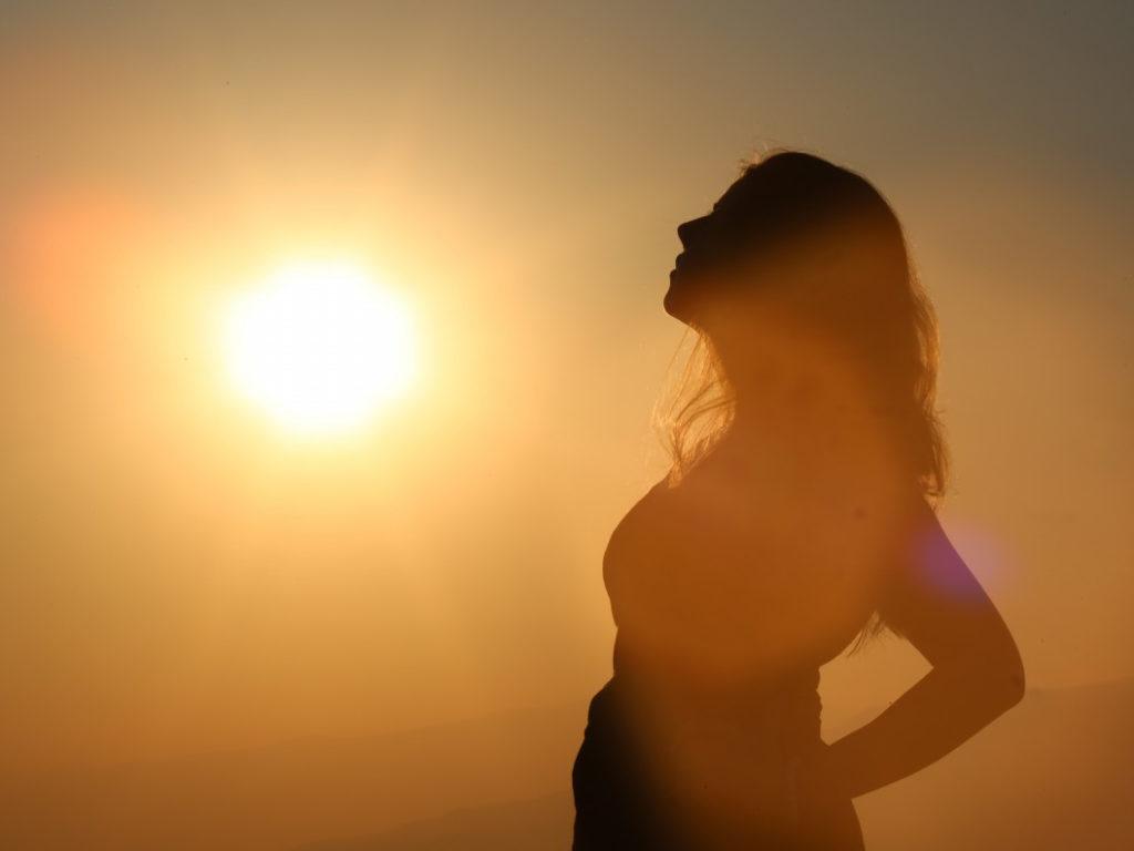 高原で朝日を浴びる妊婦