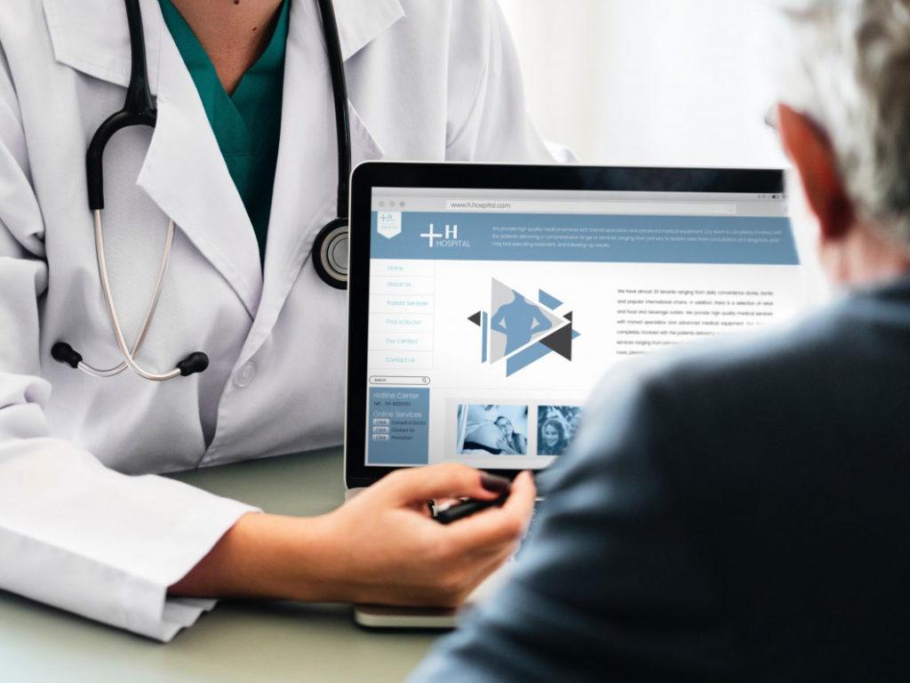 高齢者にパソコンで資料を見せながら説明する医師