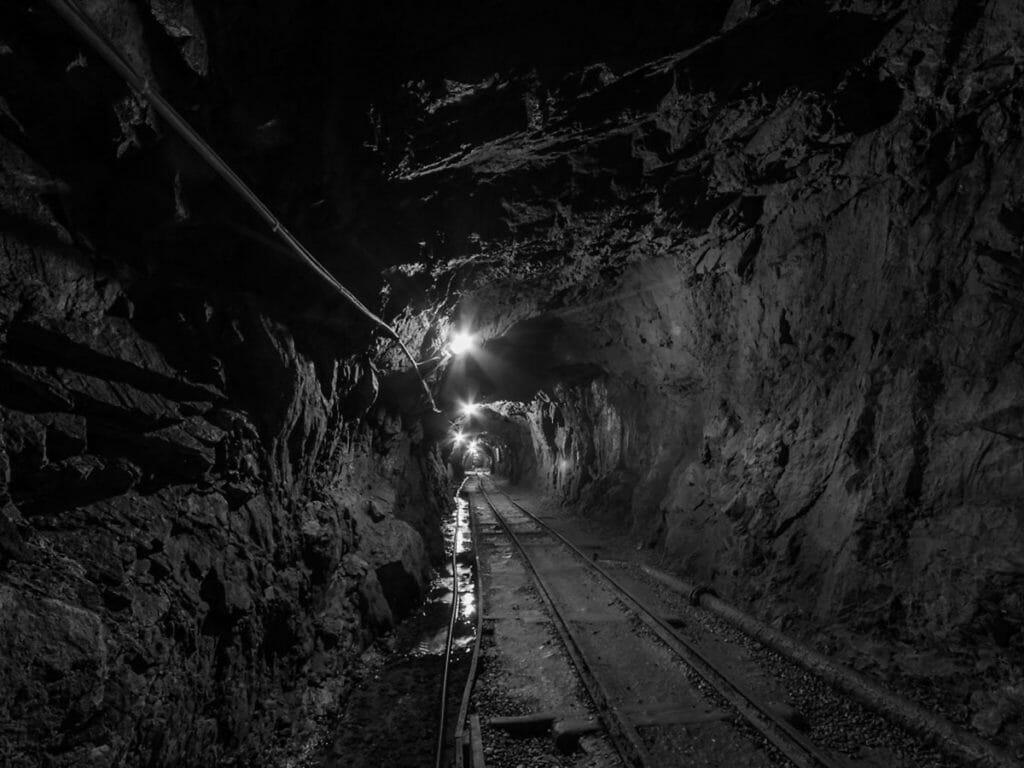 暗い炭鉱トンネルを走る電車の線路とランプ