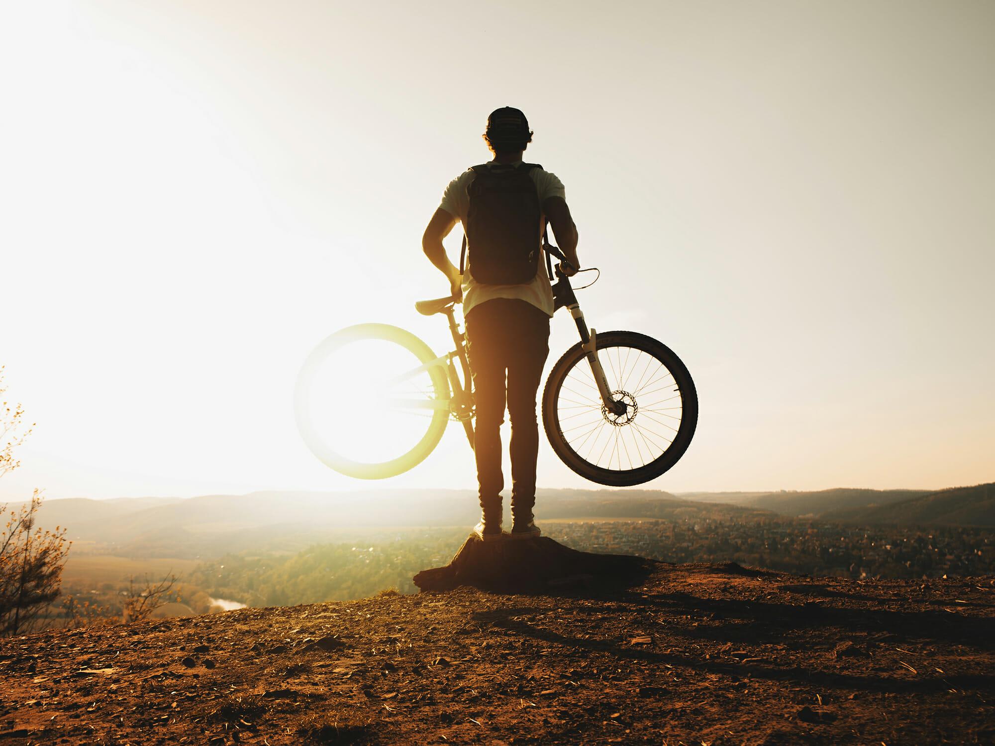 朝日を浴びながらマウンテンバイクを抱える青年