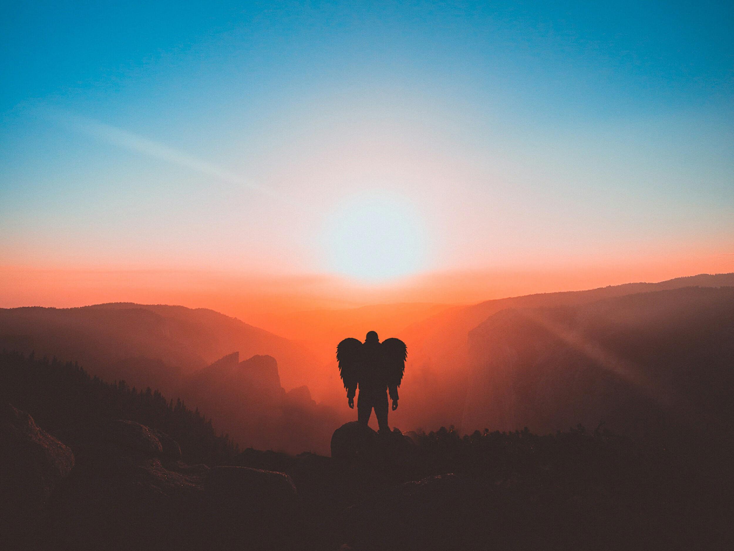 山頂に立つ有翼の男性 夜明け